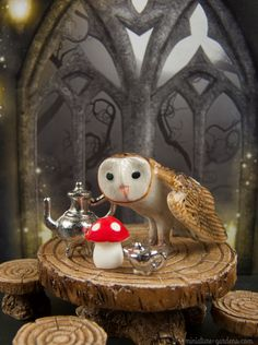 Mini Owl sips a cup of tea in the fall fairy garden.