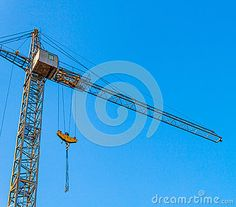 Industrial building crane on a background of the clear blue sky at sunset