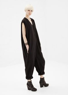 Short-sleeved, oversized jumpsuit in a black wool and viscose blend with back zip closure, 'V' shaped neckline, and side slip pockets. Dry clean.