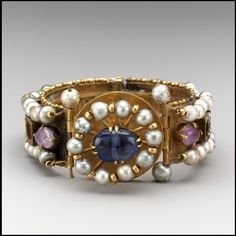"""Bracelet Byzantine, century AD The Metropolitan Museum of Art """"These elaborately decorated bracelets have richly jeweled exteriors and finely detailed opus interrasile (openwork) patterns on their interiors. The luminous beauty of pearls was. Byzantine Jewelry, Medieval Jewelry, Byzantine Art, Ancient Jewelry, Antique Jewelry, Vintage Jewelry, Wiccan Jewelry, Ancient Bracelet, Antique Brooches"""