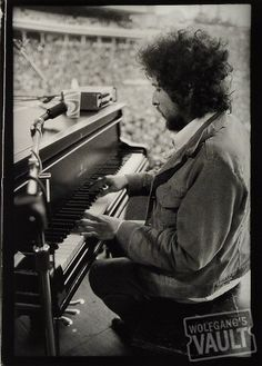 Bob Dylan. S.N.A.C.K., Students Need Athletics, Culture and Kicks, was a Bill Graham organization in theme and spirit. This one-day festival, on March 23, 1975 at Kezar Stadium in San Francisco, had Dylan in its lengthy lineup of more than 20 performers. Photographer Michael Zagaris snapped this photo from the stage of Dylan playing piano for the crowd of 50,000.