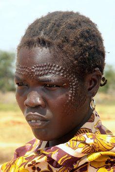 Uganda.. Karamoja - Jie tribal woman with a lot of scarifications on her face.