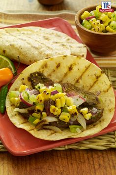 Grilled beef tacos get fiery heat in this delicious taco recipe. A marinade featuring garlic, cilantro, lime juice and three peppers brings bold flavor to grilled beef. Serve the tacos with a refreshing salsa of grilled corn, tomatillos and cilantro for a dinner recipe that's sure to be a crowd-pleaser.