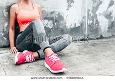 Fitness sport woman in fashion sportswear doing yoga fitness exercise in the city street over gray concrete background. Outdoor sports clothing and shoes, urban style. Sneakers closeup.