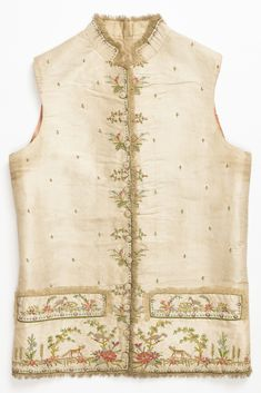 Cream-white taffeta waistcoat embroidered in multi-colored silks using chain stitch. Legend of the Fox and the Crow across bottom and pocket flap. Sprays of flowers on buttonholes. Late 18th century style waistcoat with a straight bottom and standing collar. Narrow silk fringe edges on front and collar. Twelve buttons.
