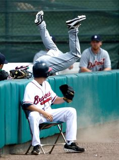 Detroit Tigers outfielder Clete Thomas flips over the left field foul wall while making a catch on a ball hit by Atlanta Braves' Michael Bourn in the first inning of spring training baseball game, Saturday, March 3, 2012, in Lake Buena Vista, Fla. The Tigers won 2-0. (AP Photo/Julio Cortez)
