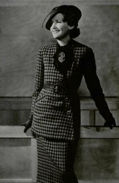 L'officiel de la Mode. Fevrier 1935. Jean Patou.    Tailored in coarse brown and green jersey. Blouse in brown woollen trimmed with a brown scarf with green monogram.