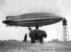 Nederlands: Het Engelse luchtschip / [zeppelin] R-100 aan de landingsmast vlak voor de reis naar Canada vanuit Bedfordshire, [28 juli 1930 of 30 juli 1928]. De R-100 heeft een nieuwe neus en staart. Voorgrond: hooien / hooiwagen.  English: The English airship / Zeppelin R-100 attached to the mooring mast in Bedforshire, just before its journey to Canada, July 1928.