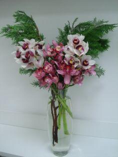 Vaso com arranjo de orquídeas Cymbidium coloridas e Túia.
