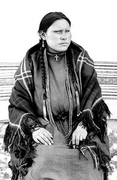 She Went Through a Crowd, a Native American Sioux woman, posed outside on a fur skin rug over the snow covered ground, Pine Ridge Agency, South Dakota. Date 1891.