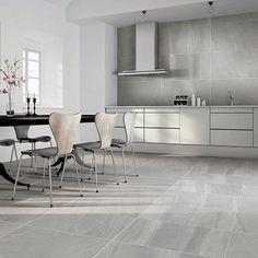 This modern kitchen features Porcel-Thin LASCAR grey blue volcanic ash effect thin porcelain tiles in a matt finish. Large Floor Tiles, Wall And Floor Tiles, Grey Marble Tile, Volcanic Ash, Kitchen Tiles, Blue Grey, Porcelain Tiles, Dining Table, Flooring