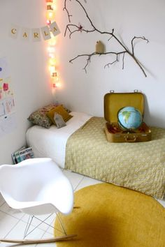 Such a cute autumnal room. We love the circular mustard rug and the added detail of the twig-wall and fairy lights!