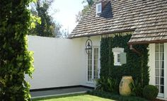vine covered wall, terra cotta urn, shutter, roof -all charming