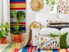 Colorful, embroidered cushions and rugs, shown together with a white sofa.