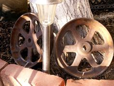 2 nice Antique iron Cart wheels nice rustic art or for yard or home decor. Vintage industrial Art online these for for much much more. seen for $40-$75 ea!  https://www.etsy.com/listing/193081526/antique-iron-wheel-industrial-cart-wheel?ref=shop_home_active_3