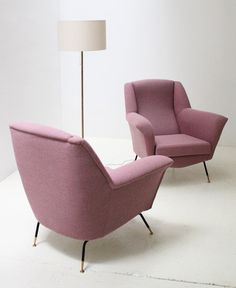 A pair of sculptural italian armchairs from 1950's. Reupholstered with new Kvadrat fabric, brass and lacquered metal legs.
