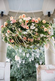Classic Chandelier with Roses & Greenery. This classic floral chandelier, created by Kim Starr Wise, is filled with peach-and-pink roses. Hanging candles are suspended below for an extra dash of romance.
