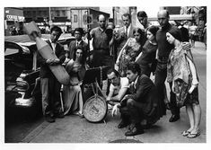 Left to right: Nam June Paik, Charlotte Moorman, Takehisa Kosugi, Gary Harris, Dick Higgins, Judith Kuemmerle, Kenneth King, Meredith Monk, Al Kurchin, Phoebe Neville. In front, kneeling, Philip Corner and James Tenney. [Photograph © Barbara Moore/Licensed by VAGA, NY.]