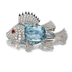 AQUAMARINE AND DIAMOND FISH BROOCH. The body set with a large cushion-shaped aquamarine bordered by calibré-cut aquamarines of conforming shape, the head and fins set with round and single-cut diamonds weighing approximately 2.50 carats, the top fin edged in calibré-cut sapphires, the eye set with a round cabochon ruby, mounted in platinum.