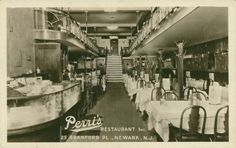 Handsome unused c. 1930s real-photo postcard of the interior of Perri's Restaurant at 25 Branford Pl. in Newark, NJ!  Nicely detailed and sharply focused, great clarity.  Lots of cigars for sale in the glass display case by the cash register.  Art Deco design elements on the upstairs balcony.  A nice glimpse into a period restaurant interior, and a desirable Essex County or tobacciana collectible in excellent condition!