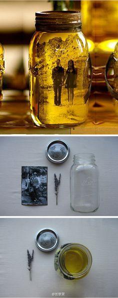 """在装满橄榄油的玻璃罐内放入一张自己喜欢的黑白照片,就可以制作出一个独特的VINTAGE""""相框""""。"""