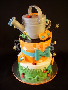"""Garden Party KAKE  Watering can and Flower pot covered in marshmallow fondant.  Bottom cake iced in buttercream.  Flowers, bugs, and other decorations are marshmallow fondant.  """"dirt"""" is oreos :)"""