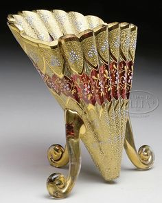Rare Moser Decorated Fan Vase Has Vertically Ribbed Cranberry Glass Body With Gilded Decoration At Bottom And Top Of Each Rib Which Is Further Decorated With Cream Colored Enamel Scrolls And Blue Stylized Flowers, Center Section Of Each Rib Has Cranberry Glass Background And Delicately Enameled White And Yellow Flowers With Cream Colored Leaves And Gold Stems, Finished With Three Applied Gilded Scroll Feet  -  James D. Julia, Inc. Auctioneers