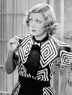 The Awful Truth (1937) - Irene Dunne as Lucy Warriner wearing a black long dress; the balloon-sleeved sheer blouse is embellished with a geometric white motif. The tie collar is decorated with a diamanté bow-shaped brooch.  The costumes were designed by Robert Kalloch.