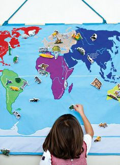 Hanging fabric world map. You can add sets of people, landmarks and animals that can be moved around. Love this!