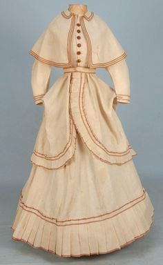 Lady's summer day ensemble, 3-piece natural linen trimmed with fawn passementerie, having polonaise bodice decorated with pleats at the cutaway hem and small peplum back, capelet with collar, full skirt with pleated hem ruffle, unlined, 1869