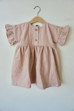 This Loa dress matches our Mommy Dress. Made out of a Linen/Cotton. There are 2 wooden button on the front and flutter belle sleeves. Perfect with tights or knee highs! Handmade in Phoenix, AZ from domestic and imported materials. This adorable dress features linen produced in the USA so