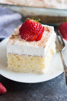 One small, square slice of tres leches cake on a white plate with strawberries fanned out on top.
