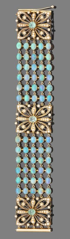 An opal, demantoid garnet and half pearl braclet.  The bracelet designed as five rows of collet-set cabochon opals, between square openwork by どえふ