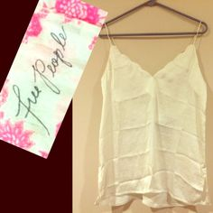 nwt - FREE PEOPLE top brand new! in serious need of a good steam!!!!FP intimates but can also be worn as a dressy top - soft, silky, flowy off-white cami with spaghetti cross back / scalloped neckline/ detailed bottom and small slits up sides ---- only flaw is a light lip gloss mark on the inside bottom which isnt visible from front - this could be easily removed Free People Tops Blouses