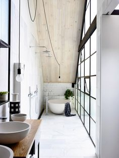 bathroom with industrial style windows and free standing contemporary battub
