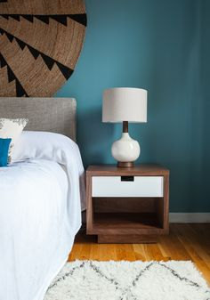 Gus Modern walnut end table, mid-century modern inspired ceramic table lamp and round jute rug as wall decor (both Westelm)