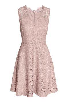 Een mouwloze jurk van opengewerkt kant met een V-hals, een naad in de taille en een uitlopende rok. De jurk heeft een blinde ritssluiting achter. Gevoerd me