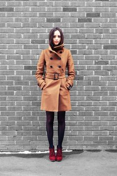 High collar camel coat, black tights, red lace-up booties