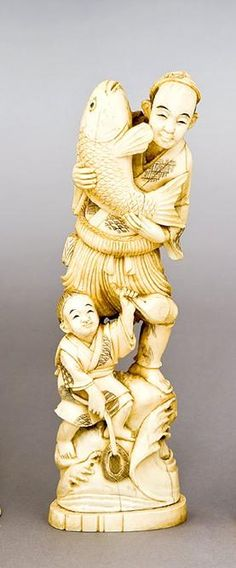 A Japanese ivory figural group of a fisherman holding a large carp, standing midst swirling waves, a child at his feet, incised signature to base, some damage, 26.5 cm high