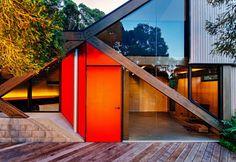 Arancio vitaminico per la porta d'ingresso che conduce alla zona giorno dell'abitazione immersa nella foresta poco fuori Victoria, in Australia. Lo studio Maddison Architects ha creato una facciata tutta vetro rivolta verso il mare