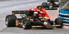 Mario Andretti gives team mate Gunnar Nilsson a lift back to the pits Long Beach 1977