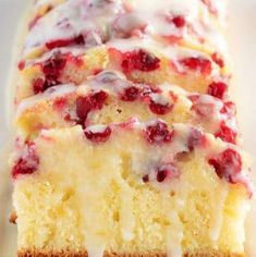 Baked and sliced loaf of orange cranberry bread drizzled with orange glaze.