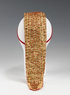 Headdress (back view) | Probably Albanian, late 19th century | Materials: cotton, metal, coral | This unique piece of headwear, with its serpent form, may have been some kind of talisman to ward off evil spirits. It is notable for its intentionally representational design | The Metropolitan Museum of Art, New York