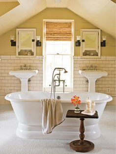 His-and-hers pedestal sinks flank a window and act as a backdrop to the dramatic centerpiece--a vintage-style soaking tub. myhomeideas.com