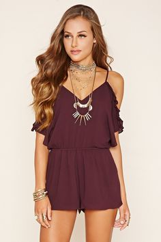 A woven romper featuring open-shoulder short sleeves with ruffled flounce layer trim, adjustable cami straps, a V-neckline, a deep V-back with a self-tie strappy accent, an elasticized waist, and side slip pockets.