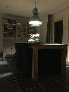 Voormalige keuken wordt eethoek met taupekleurige buffetkast en industriële lamp.
