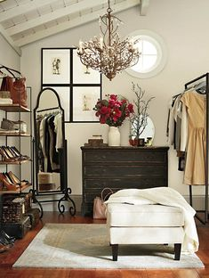 love the layout; small room turned closet; hanging rack, open shelves, ottoman, dresser, mirror, fresh flowers, mirror; closet atmosphere.