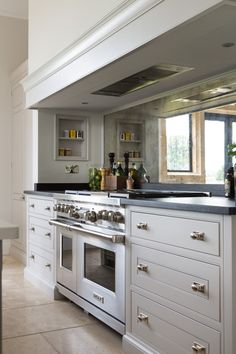 Mirrored Splashback & Wolf Range Cooker at The Grange, Ascot Project | Humphrey Munson. Mirrored splash back nice, as are the in built shelves above the cooker.