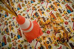 Buy some construction fabric for a table cloth or runner OR find some wrapping paper to cover table