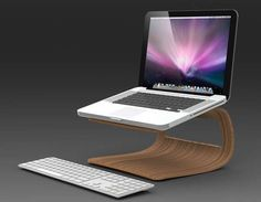 This laptop holder is very similar to one specific stand. It has the same basic shape to it except for the wood cut out at the back of it. It allows the person to have the laptop at a pretty high level meaning it ensures that the person sits straight while they are working. Even though this stand doesn't have space for a keyboard, it allows them to use a keyboard on the table. It has a very simple brown colour and is also made of bamboo/wood.
